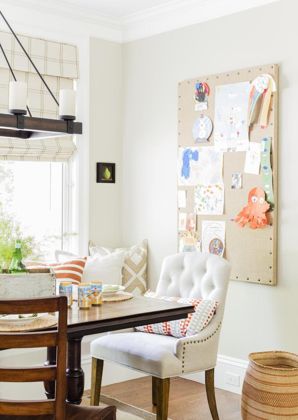 A burlap bulletin board displays kids' art.